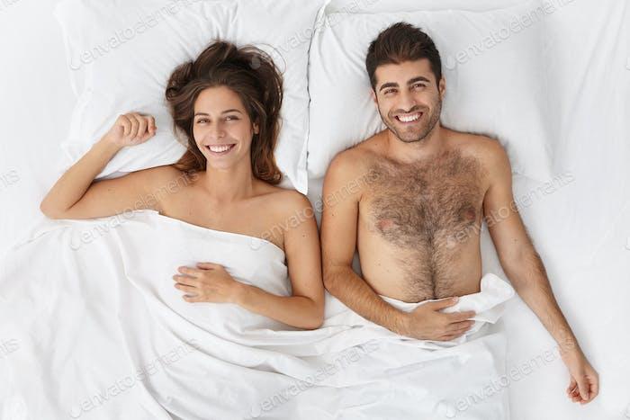 Glückliche Jungvermählten verbringen wundervolle Hochzeitsnacht zusammen, haben eine tolle Stimmung als Erwachen am Morgen.  F