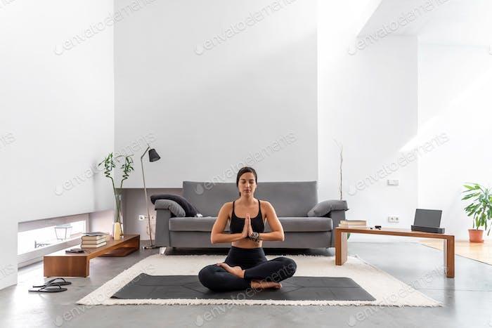 Attraktive Frau praktizieren Yoga Lotus Pose Meditation in gemütlichem Zuhause