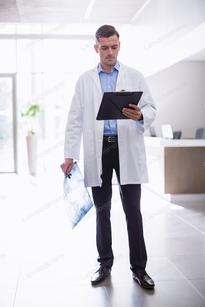 Doctor standing with clipboard in corridor