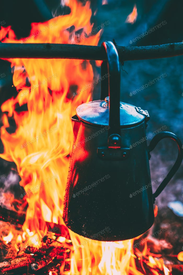 Old Iron Camp Kettle Boils Water On A Fire In Forest. Bright Fla