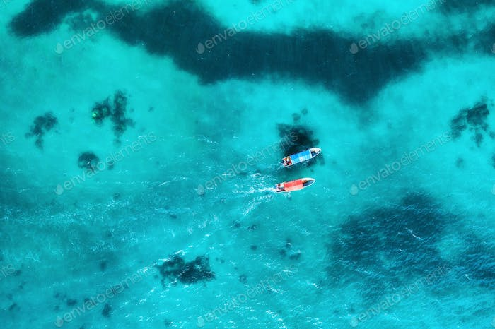 Aerial view of the fishing boats in transparent blue water