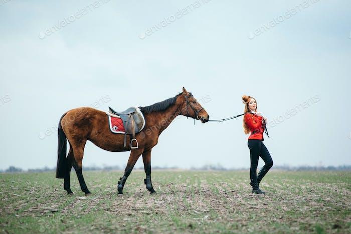 rothaarige Jockeymädchen in einer roten Strickjacke und schwarzen hohen Stiefeln mit einem Pferd