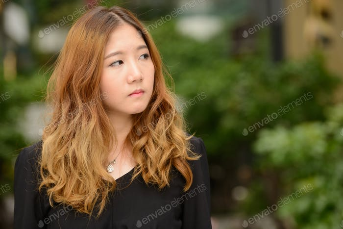 Face of young beautiful Asian businesswoman thinking at the park