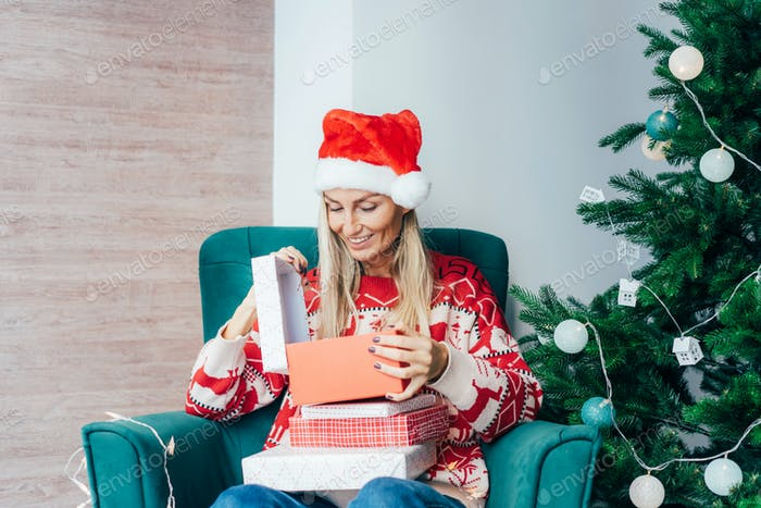 Happy smiling blonde opens a gift box. Christmas gifts and miracles.