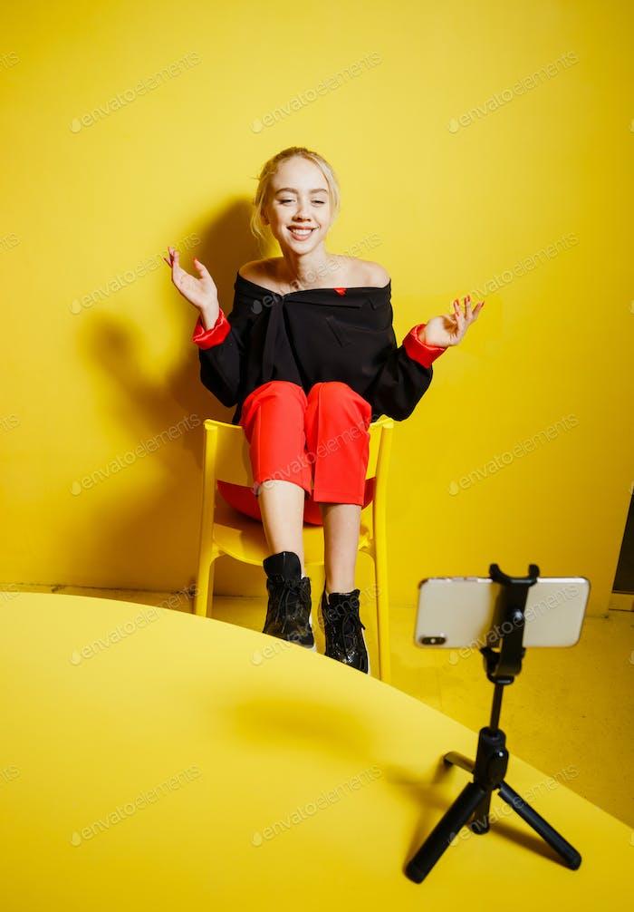 Junge Mode Mädchen Blogger gekleidet in roten Hosen und schwarze Jacke nimmt ein Selfie auf dem Smartphone