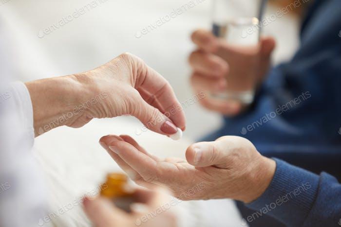 Giving Pills to Senior Man