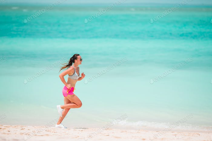 Fit young woman on the tropical beach in sportswear