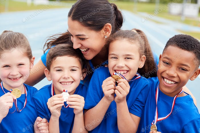 Children With Female Coach Showing Off Winners Medals On Sports Day