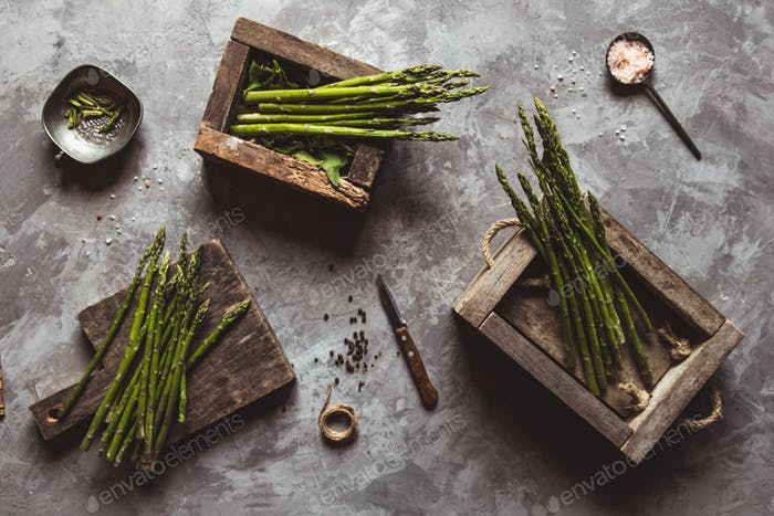 Asparagus on a cutting board in a wooden box. Healthy food, health on a concrete background