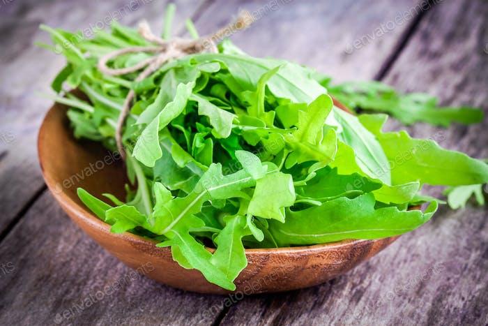 organic arugula bundle in a wooden bowl