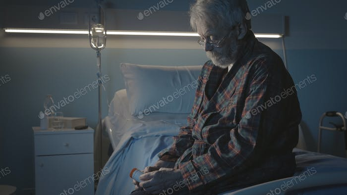Senior man sitting in a hospital bed and holding a pill bottle