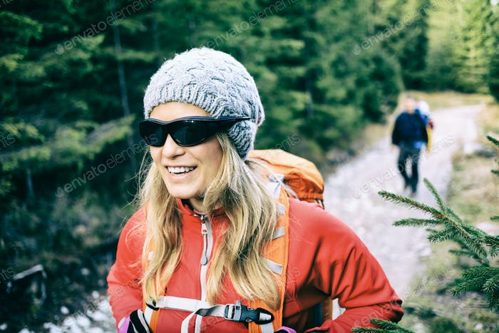 Couple hikers walking on trail in forest
