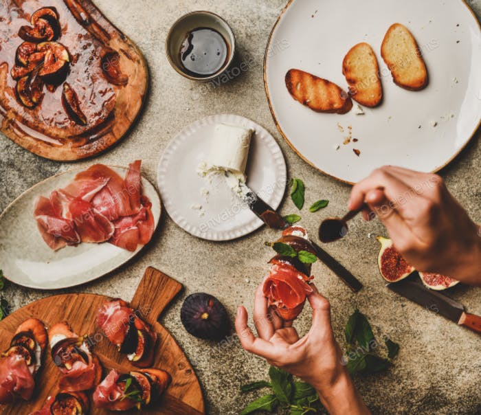 Crostini with prosciutto, grilled figs, cheese and hands with canape