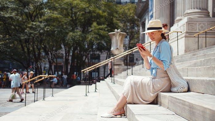 Mujer atractiva con teléfono en los escalones de un edificio
