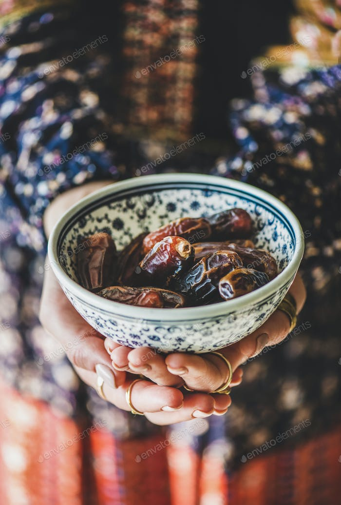 Woman holding bowl of dates for Ramazan Iftar fasting meal
