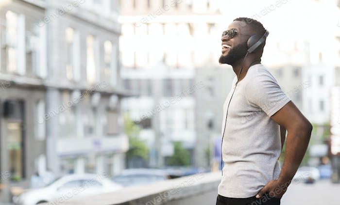 Fröhliche afrikanische Kerl in Kopfhörer genießen Musik hören