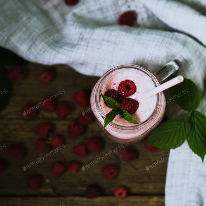 Pink raspberry smoothie in a mason jar with straws on a rustic wood background