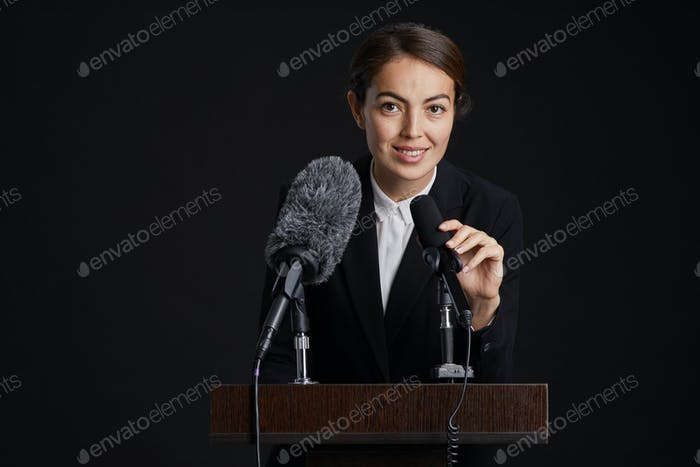 Smiling Female Speaker at Podium