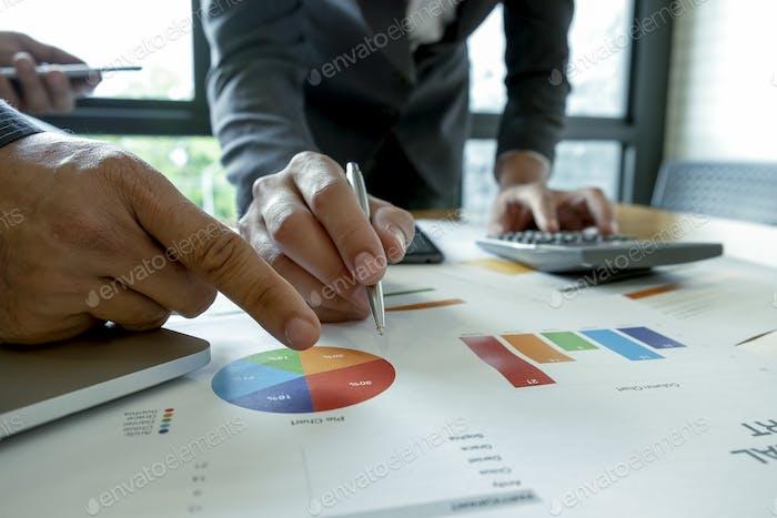 Business-Team analysiert Diagramme auf dem Schreibtisch.