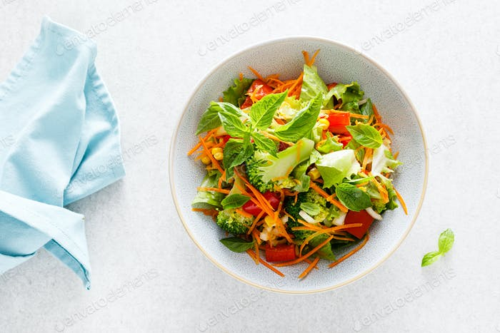 Fresh raw vegetable salad with boiled broccoli, greens and vegetables