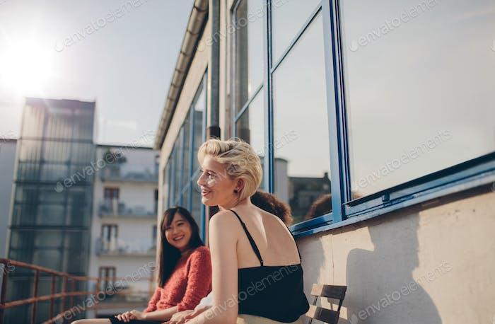 Drei junge Frauen sitzen auf dem Balkon