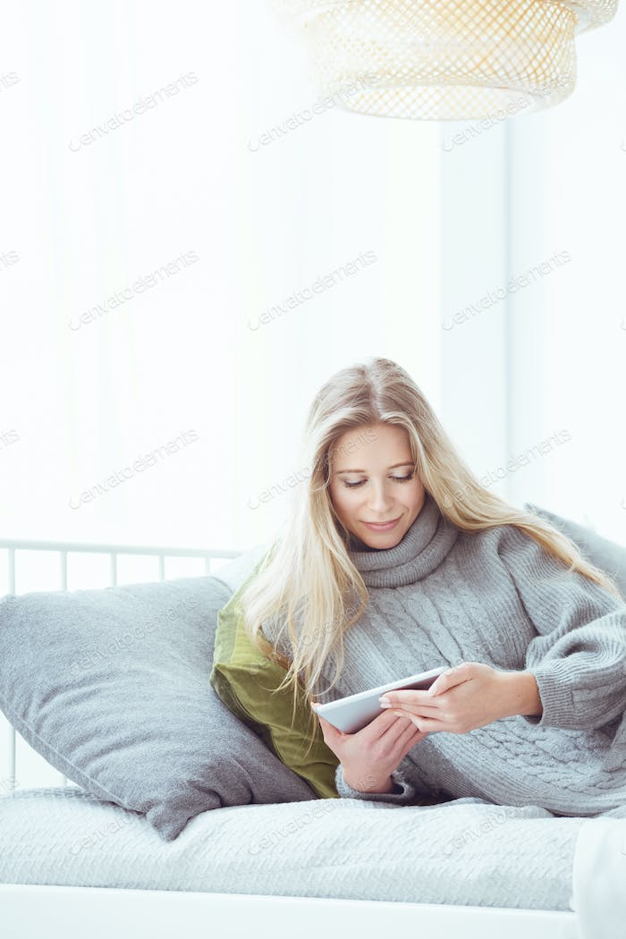 Woman using cell phone in bed