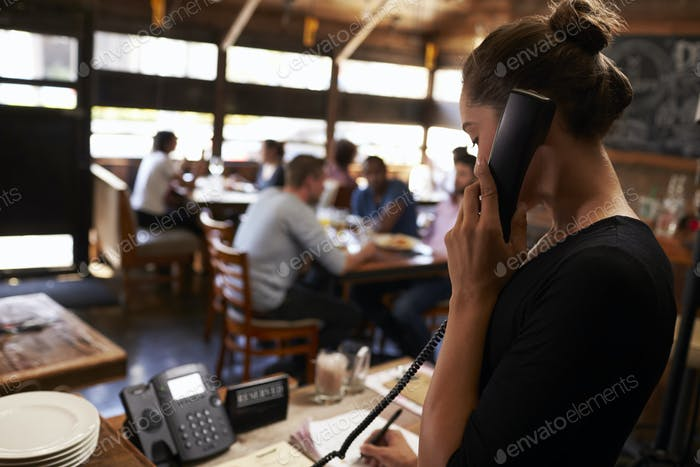 Young woman taking a reservation by phone at a restaurant