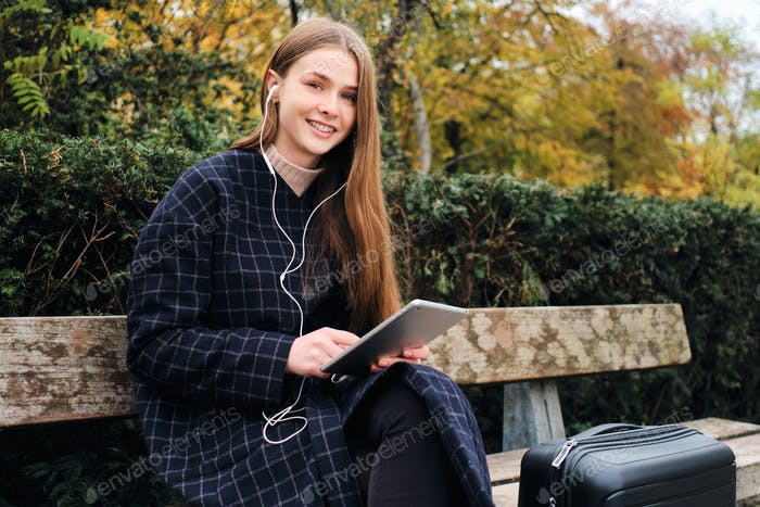 Pretty smiling girl with suitcase happily using tablet resting on bench in park