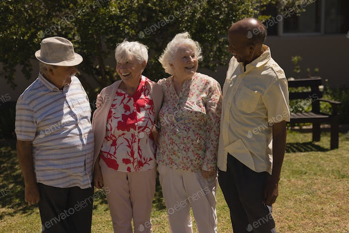 Front view of happy senior friends interacting with each other in garden