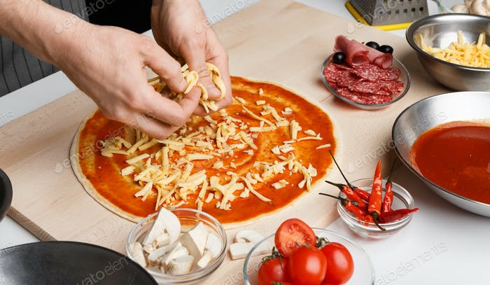 Italian dish. Chef adding grated cheese to pizza