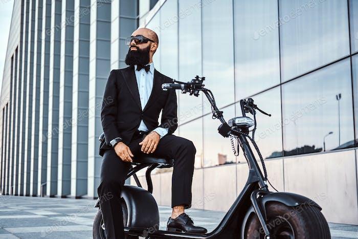 Современный человек сидит на своем новом электро скутере