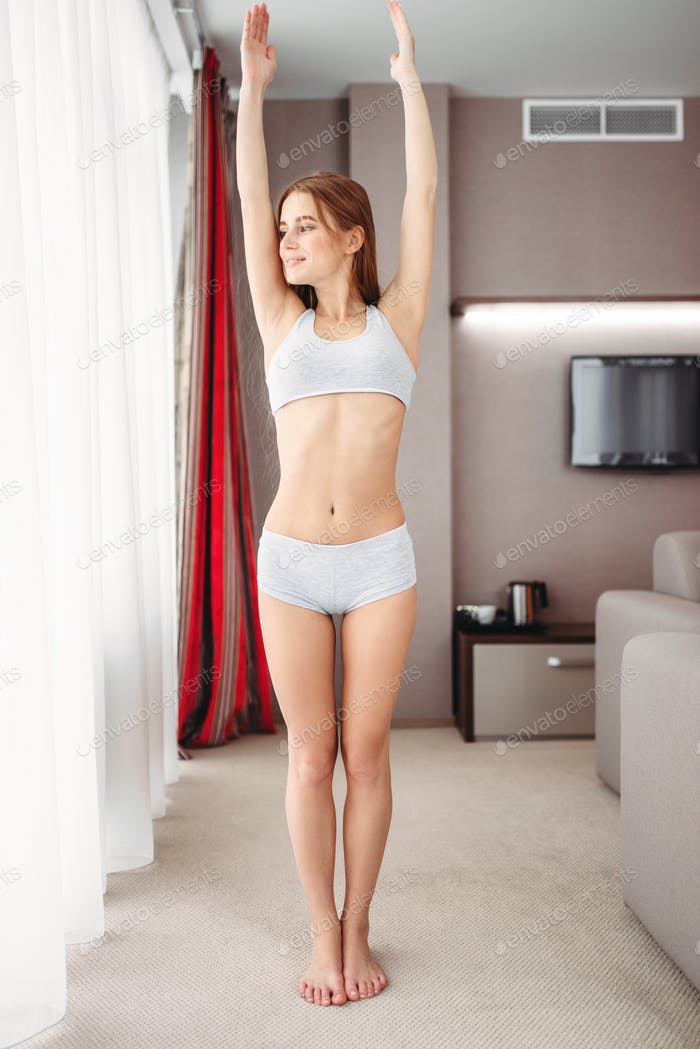 Woman doing morning exercise in bedroom, waking up