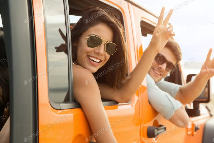 Happy friends sitting in a car and showing peace gesture