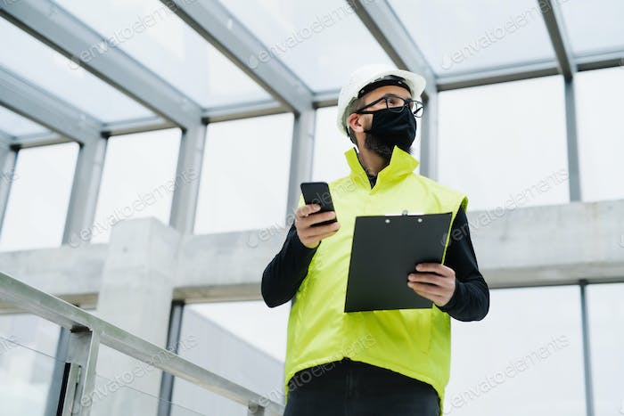 Portrait of worker with face mask at the airport, holding smartphone