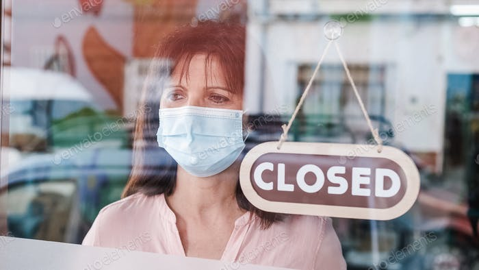 Mujer convirtiendo un cartel de abierto a cerrado. Covid-19.