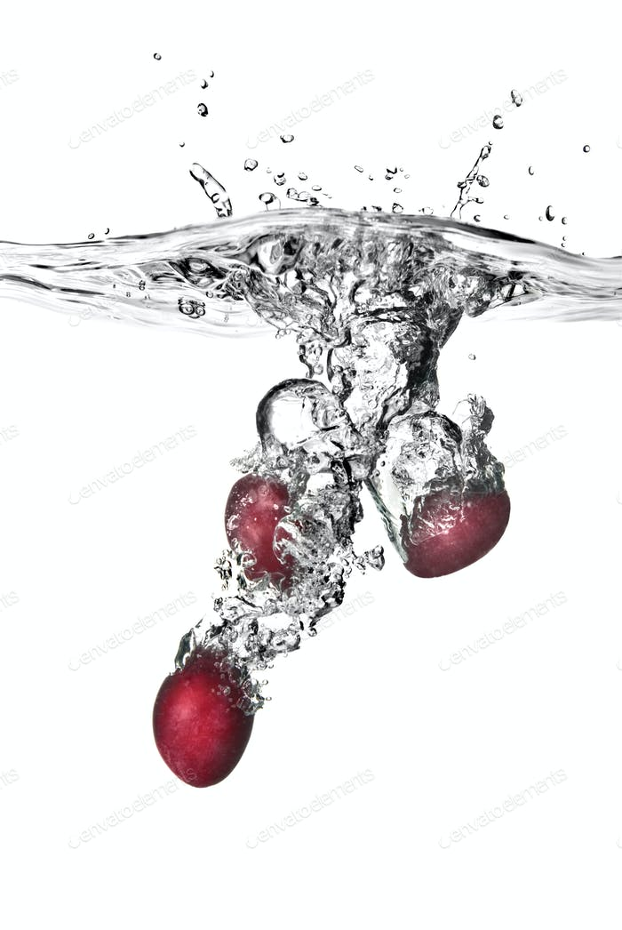 plum dropped into water with bubbles isolated on white