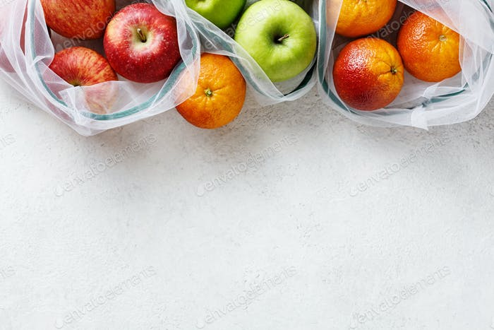 Fresh fruits in reusable bags, copy space