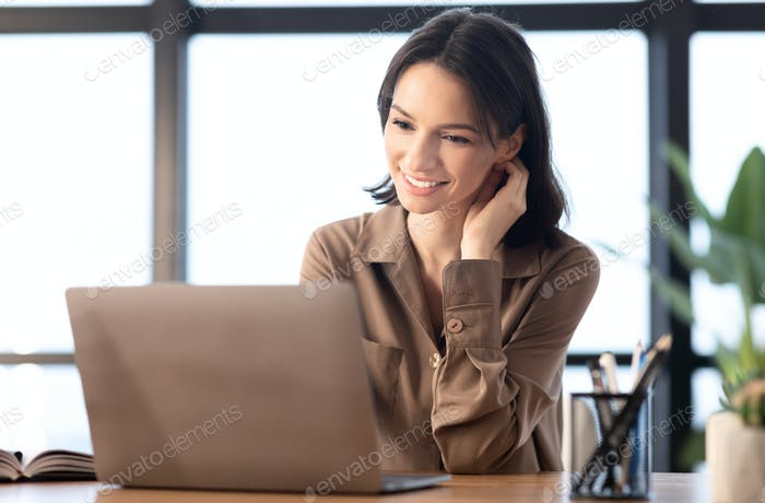 Young manager looking at laptop in modern office