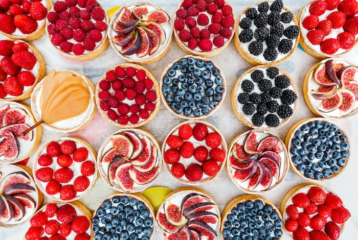 Fruit and Berry tarts dessert assorted top view background