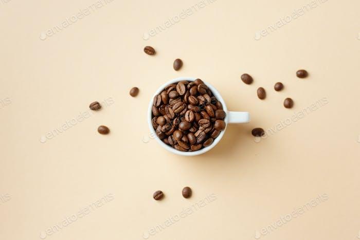 Kaffeebohnen in Tasse auf Pastell