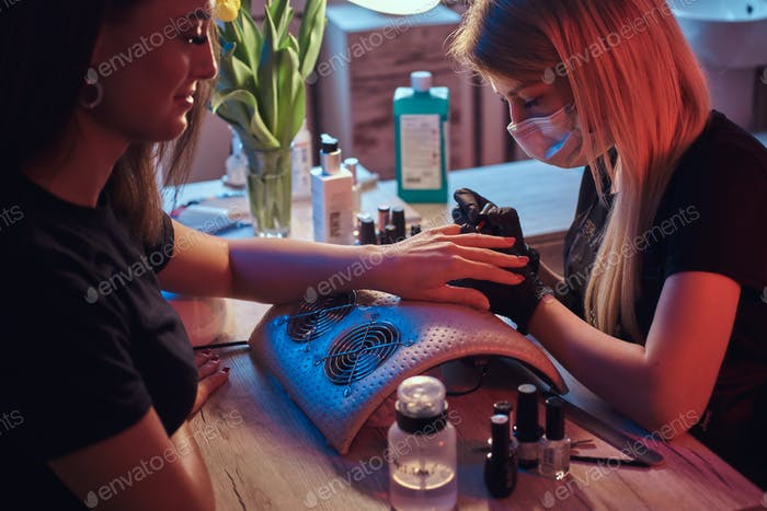 Master manicure applying polish on client's natural nails in the beauty salon.