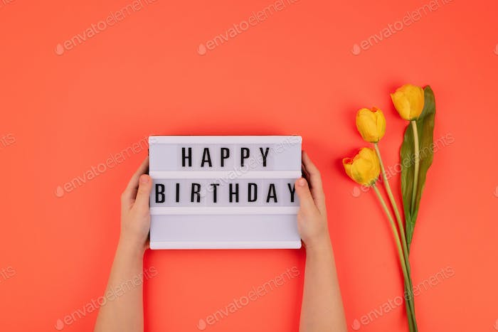 Happy birthday flat lay. Children hands holding light box with text Happy birthday and bouquet of