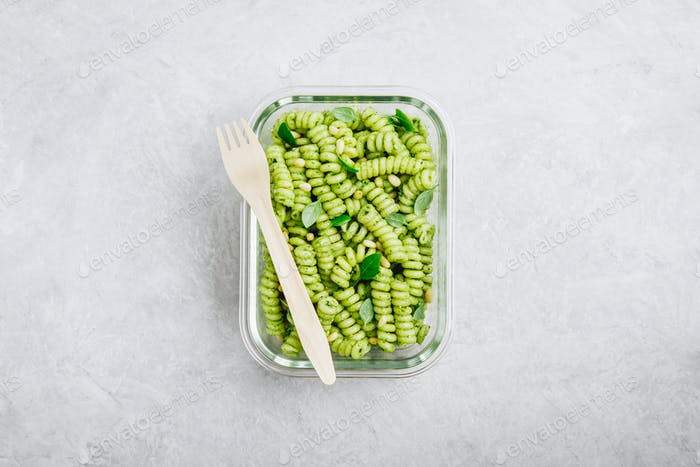 Vegetarian meal prep containers green pesto pasta with basil and pine nuts.  Top view