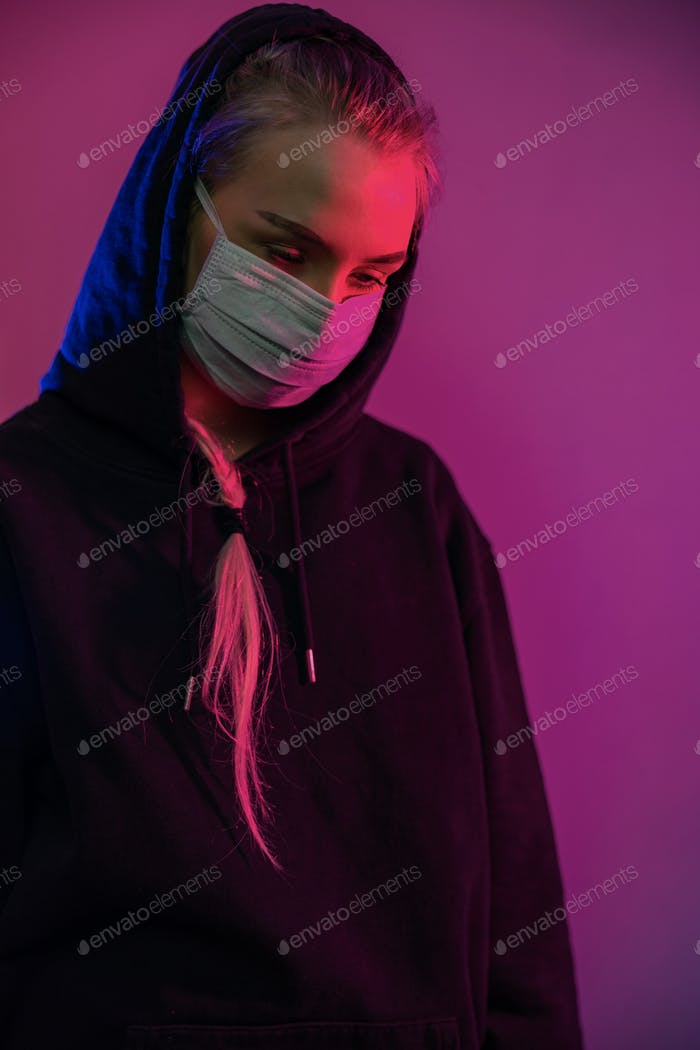 Exhausted or depressed woman in protective face mask with multi colored lights
