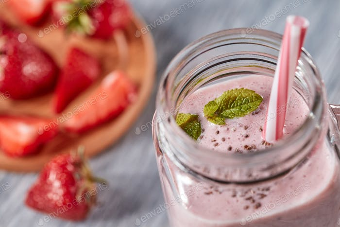 Closeup of organic milky strawberry smoothie with chia seeds and mint leaves in a glass with a straw