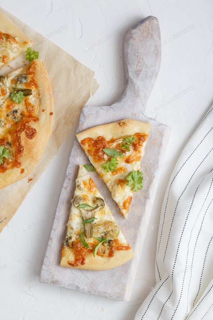 two pieces of white pizza with artichoke and arugula