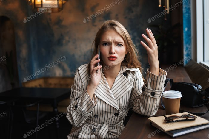 Young woman in striped trench coat emotionally talking on cellph