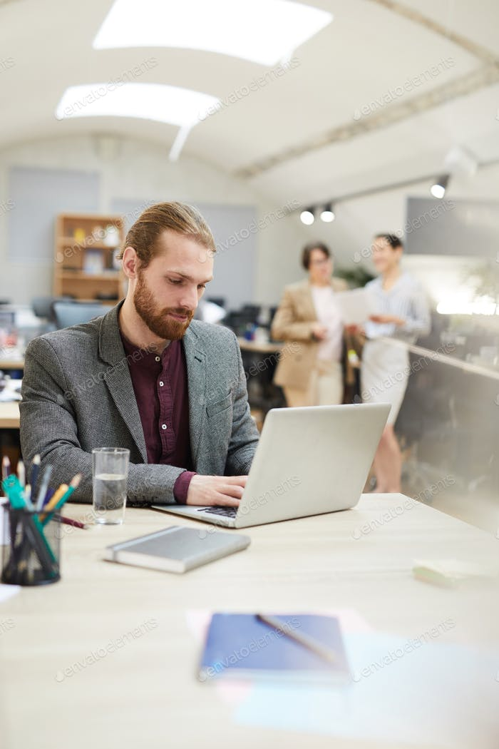 Businessman Using Laptop in Open Space Office