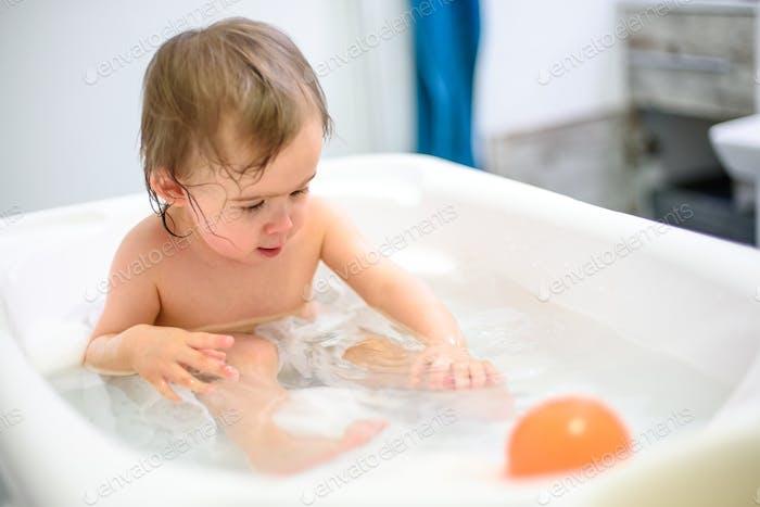 1 year old Baby in bathtub taking bath in bathroom