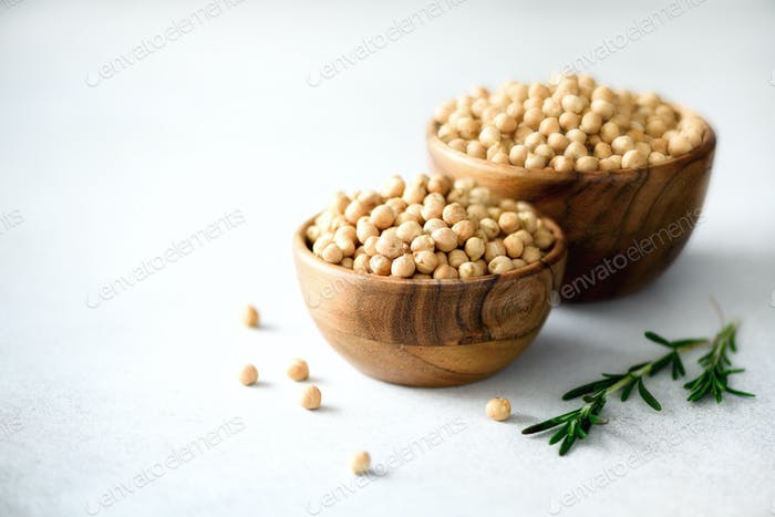 Organic raw chickpeas in wooden bowls and rosemary on gray concrete background. Healthy food